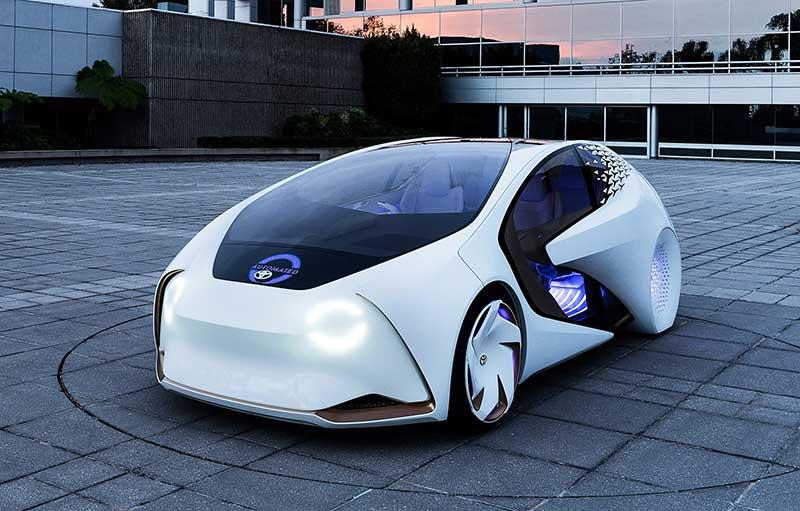 现代化建筑的外面停着的白色CONCEPT-爱 i正在发光。被称为YUI的人工智能信号功能会让车身外侧的车灯闪烁,给其他驾驶员发送信号,以保证安全行驶。
