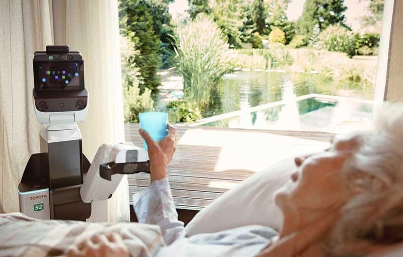 Human Support Robot正在给坐在床上,面带微笑的年长女性递水。
