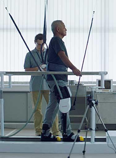 正在接受治疗的男性在Physical Rehabilitation Aid Robot跑步机上进行行走练习。底部到顶部都使用悬架安全带进行固定支撑。